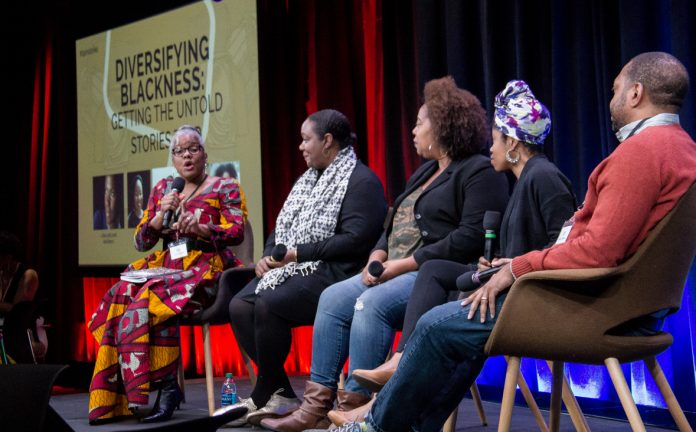 People seated onstage engaged in a panel discussion