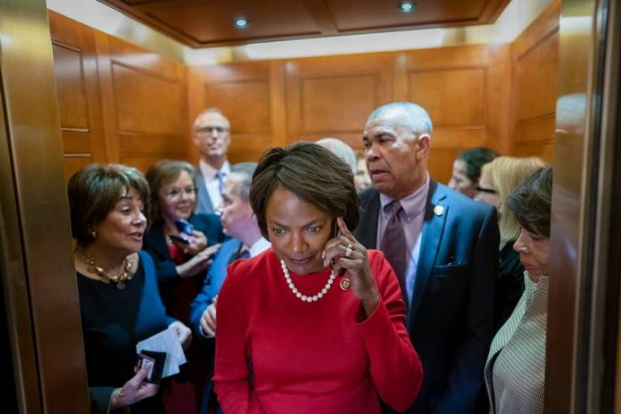 Val Demings in red standing in an elevator