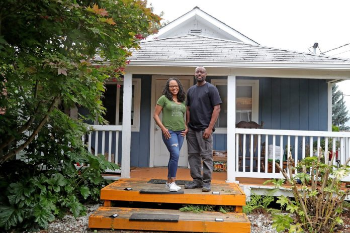 Black homeowners in front of their home