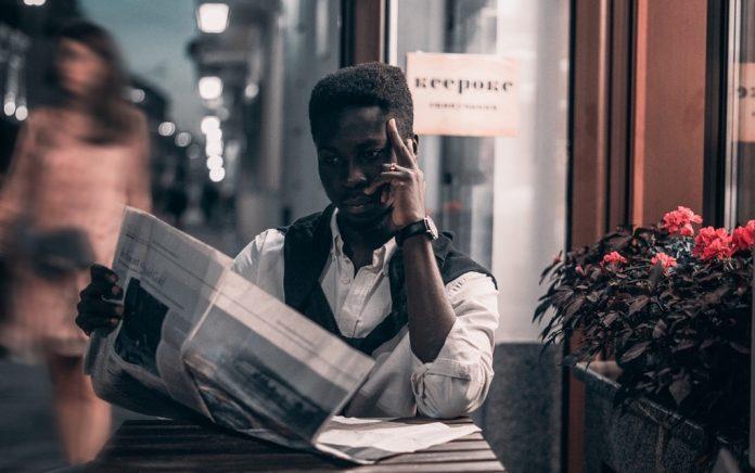 Black man reading newspaper
