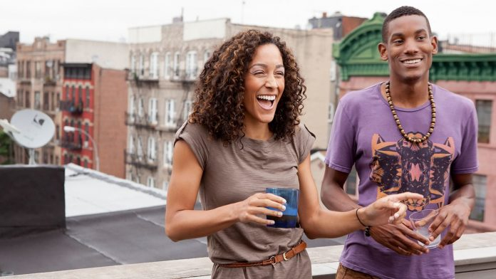 Two young people laughing atop a roof