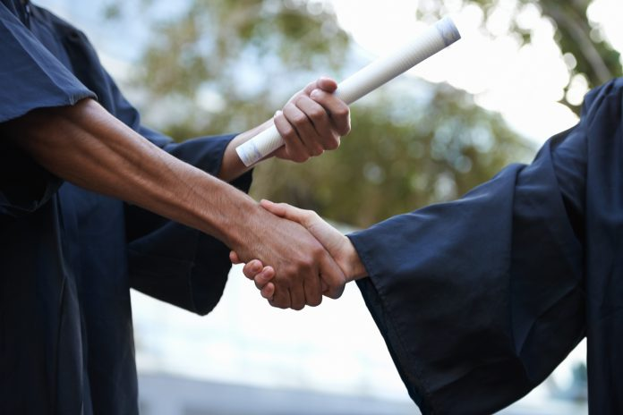 two graduates shaking hands