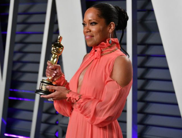 Woman in red holding an Academy award