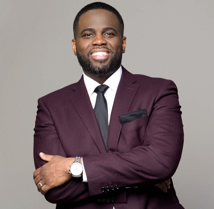 Man smiling in a burgundy suit