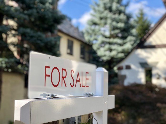 Home with a For Sale sign out front