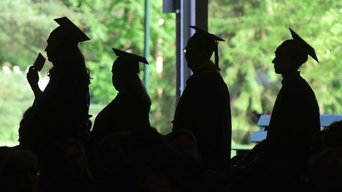 A procession of grads dressed in gowns