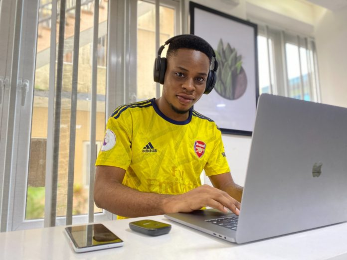 Boy in a yellow shirt at a laptop