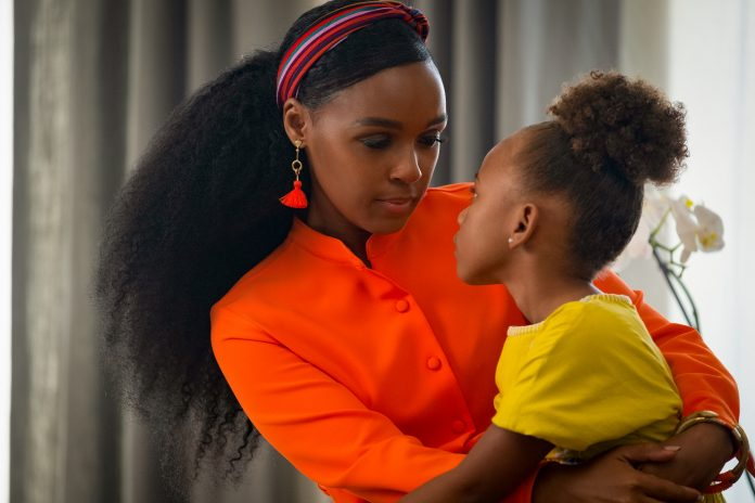 Woman in bright orange shirt holding a little girl