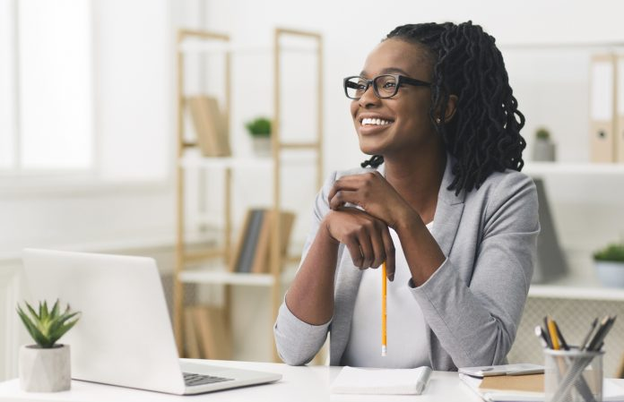 Black woman smiling seated at a desk