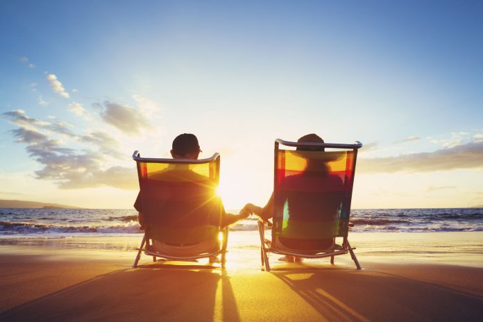 Two people seated in beach chairs on the sand