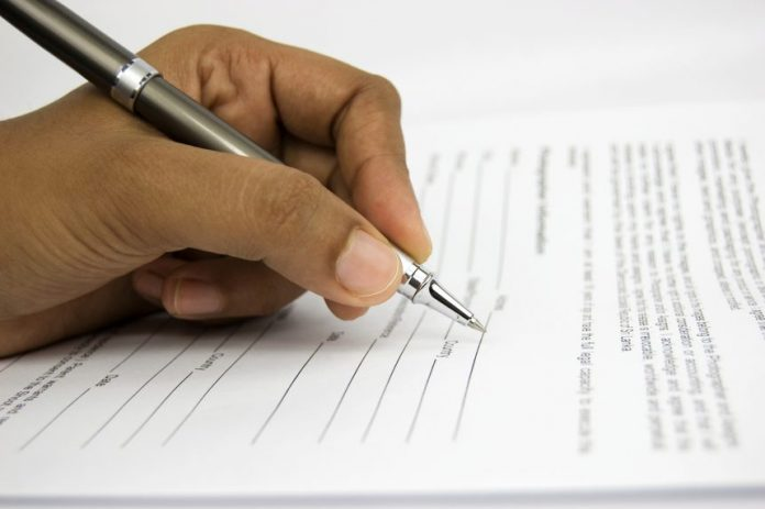 man signing a page
