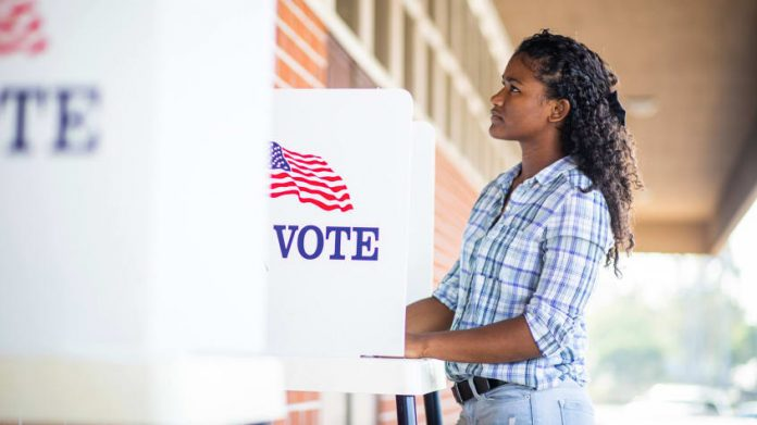 woman standing in a voting booth