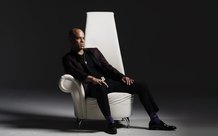 Man seated in Black suit in white chair
