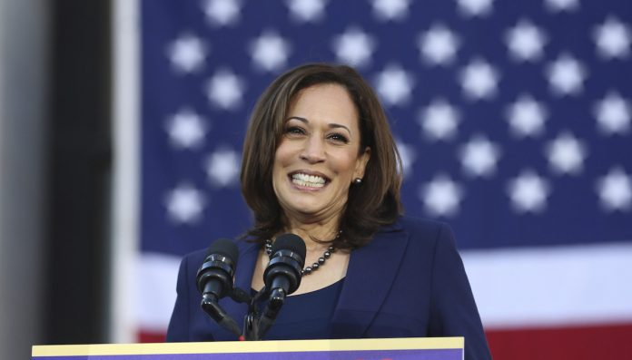 Kamala Harris smiling with the American flag in the backdrop