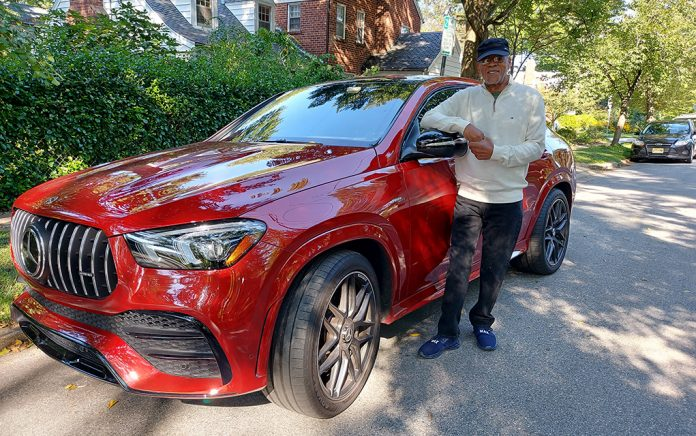 Man standing in front of a red SUV