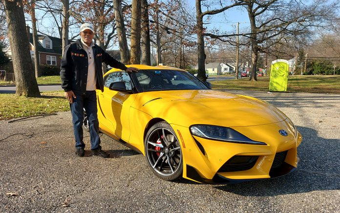 Man standing beside yellow sports car